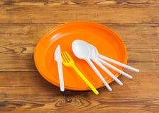 Plats, cuillères, fourchette et couteau en plastique jetables sur le ressac en bois Photo stock