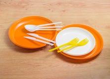 Plats, cuillères, fourchettes et kn en plastique jetables oranges et blancs Photo stock