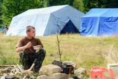 Plats d'un homme tout en voyageant dans la nature sur le fond des tentes photographie stock