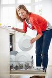 Plats de chargement de femme dans le lave-vaisselle Image libre de droits
