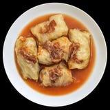 Plats de chou Rolls bourrée de la viande hachée cuite en sauce tomate avec le fond fumé de Ham Slices Isolated On Black de porc Image stock