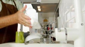 Plats de lavage d'homme fonctionnant à la maison dans la cuisine clips vidéos