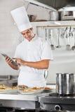 Plats de pâtes d'Using Tablet With de chef au compteur Photographie stock