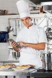 Plats de pâtes de Holding Tablet With de chef au compteur Photographie stock libre de droits
