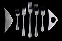 Plats de poisson poissons des fourchettes Logo sur le fond noir Images libres de droits