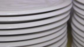 Plats de porcelaine blancs empilés, plats dans l'intérieur de cuisine de restaurant, glisseur tiré clips vidéos