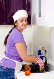 Plats de sourire de nettoyage de cuisinière de femme Images libres de droits