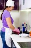 Plats de sourire de nettoyage de cuisinière de femme Image stock