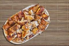 Plats de tranches de porc rôties par broche réglées sur Straw Place Mat Grunge Surface Photos stock