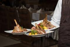 Plats de transport d'arbre de serveur avec le plat de viande sur un certain événement de fête images stock
