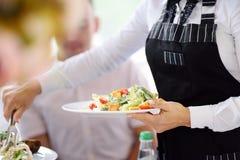 Plats de transport de serveur avec de la salade sur la réception de partie ou de mariage Photos libres de droits