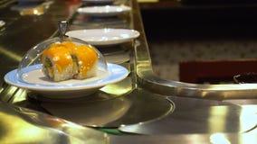 Plats du roulement de sushi et de sashimi sur la bande de conveyeur banque de vidéos