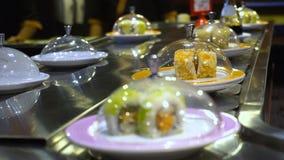 Plats du roulement de sushi et de sashimi sur la bande de conveyeur clips vidéos