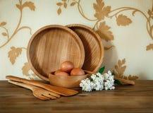 Plats en bois, équipement de cuisine Oeufs, branche blanche de lilas Woode Photo stock