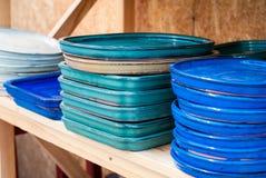 Plats en céramique colorés Soutiens des fleurs sur un fond en bois Photographie stock libre de droits