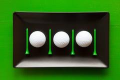 Plats en céramique noirs avec des boules de golf et des pièces en t en bois Images stock