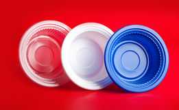Plats en plastique colorés sur le fond rouge Images libres de droits