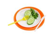 Plats en plastique jetables oranges et blancs, concombre, fourchettes et Photos stock