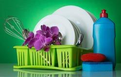 Plats et couverts propres dans le dessiccateur sur le fond vert décoré d'une branche des orchidées image libre de droits