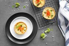 Plats et grille de cuisson avec les tartelettes saumonées savoureuses Photos libres de droits