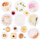 Plats et tasses sales après un repas sur le blanc Image stock