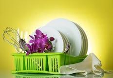 Plats et ustensiles lavés dans le dessiccateur vert sur le fond jaune, une branche d'orchidée et la vaisselle images libres de droits