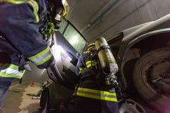 Plats för bilolycka inom en tunnel, brandmän som räddar folk från bilar Royaltyfri Bild