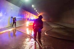 Plats för bilolycka inom en tunnel, brandmän som räddar folk från bilar Arkivbild