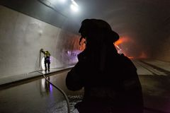 Plats för bilolycka inom en tunnel, brandmän som räddar folk från bilar Royaltyfria Bilder