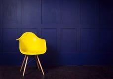 Plats för inredesign med gul stol på den blåa väggen royaltyfria foton