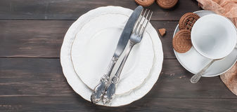 Plats, fourchette, couteau et tasse vides sur la table en bois Photographie stock