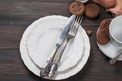 Plats, fourchette, couteau et tasse vides sur la table en bois Photographie stock libre de droits