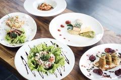 Plats gastronomes modernes mélangés de nourriture de fusion sur la table Images stock