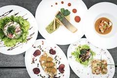 Plats gastronomes modernes mélangés de nourriture de fusion sur la table Image stock