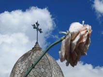 Plats i en kyrkogård: ett rostigt metallkors på överkanten av en mausoleum och en konstgjord vissen blomma ut ur fokus fotografering för bildbyråer