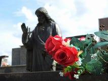 Plats i en kyrkogård: en filial av fejkar röda blommor I bakgrunden gjorde suddig en staty av Jesus Christ royaltyfri bild