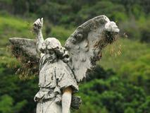 Plats i en kyrkogård: gammal staty av en ängel med brutna vingar royaltyfria foton