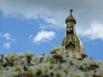 Plats i en kyrkogård: en guld- staty av vår dam och en suddig bukett av små tusenskönor arkivbilder