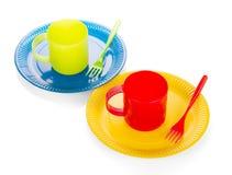Plats jetables lumineux, tasse en plastique et fourchettes d'isolement sur le blanc Image libre de droits