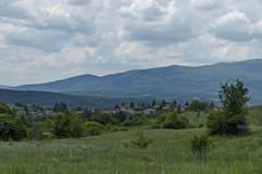 Plats med berggläntan, skogen och det bostads- området av den bulgarian byn Plana Fotografering för Bildbyråer