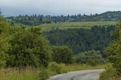 Plats med berggläntan, skogen och det bostads- området av den bulgarian byn Plana, Plana berg Royaltyfri Foto
