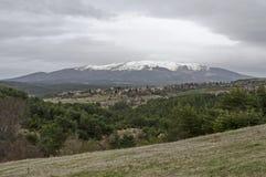 Plats med vårberggläntan, skogen, snö och det bostads- området av den bulgarian byn Plana Royaltyfri Bild
