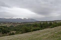 Plats med vårberggläntan, skogen, snö och det bostads- området av den bulgarian byn Plana Royaltyfri Foto