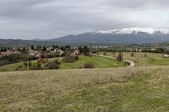 Plats med vårberggläntan, skogen, snö och det bostads- området av den bulgarian byn Plana Arkivfoto