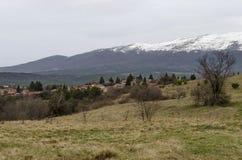 Plats med vårberggläntan, skogen, snö och det bostads- området av den bulgarian byn Plana Fotografering för Bildbyråer