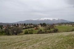 Plats med vårgläntan, skog, bostads- område av den bulgarian byn Plana i det Plana berget och det snöig Witosha berget Royaltyfri Bild