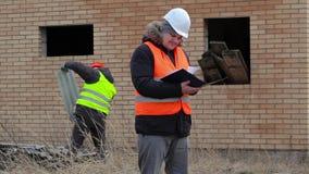 Platschef med dokumentation och arbetare i bakgrund nära byggnad lager videofilmer