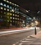 Platsen för natten för den London stadsvägen, ljus för nattbilregnbåge skuggar Arkivfoto