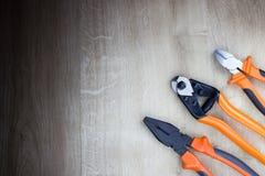 Plattång och sidoskärare som isoleras på wood bakgrund Arkivbild