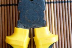 Plattång också som är bekant som pointy näsplattång eller lång näsplattång som isoleras på träbakgrund royaltyfri bild
